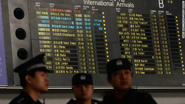 Chinese police stand beside the arrival board showing delayed Flight MH370 in red at the Beijing airport on March 8.