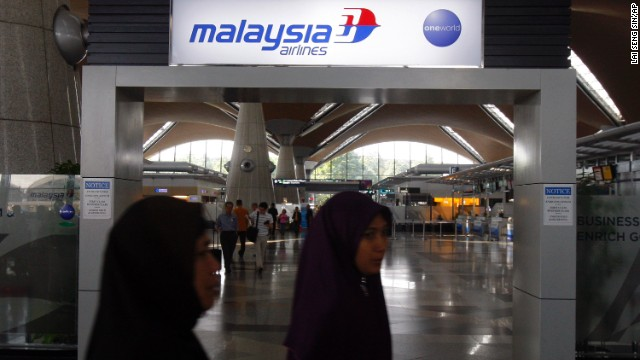 Passengers walk past a Malaysia Airlines sign on March 8 at Kuala Lumpur International Airport.