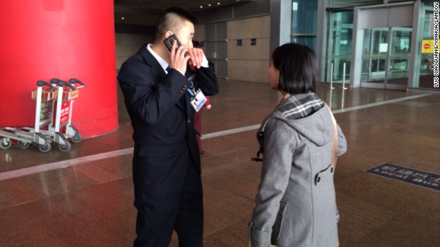 A woman asks a staff member at the Beijing airport for more information on the missing flight.