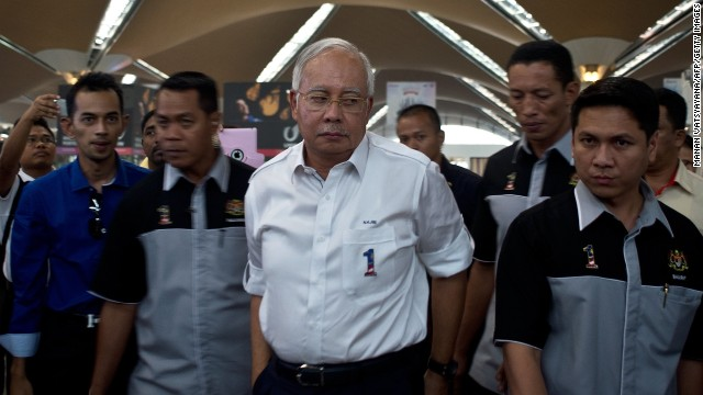 Malaysian Prime Minister Najib Razak, center, arrives to meet family members of missing passengers at the reception center at Kuala Lumpur International Airport on March 8.