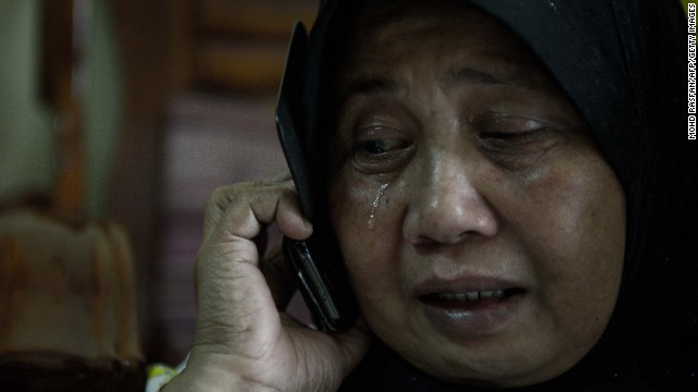 A relative of two passengers on the missing plane reacts at their home in Kuala Lumpur on March 8.