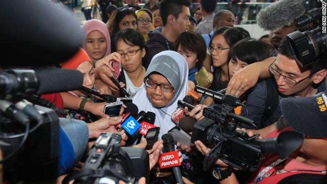A family member of passengers aboard a missing Malaysia Airlines plane is mobbed by journalists at Kuala Lumpur International Airport in Sepang, outside Kuala Lumpur, Malaysia, on Saturday, March 8.