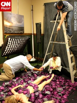 Crew members carefully place the leaves around model Camille Dauchez.