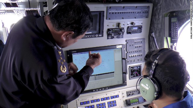 A handout picture provided by the Malaysian Maritime Enforcement Agency shows Malaysian coast guard personnel checking a radar screen during search and rescue operations for the missing Malaysia Airlines flight on March 9.