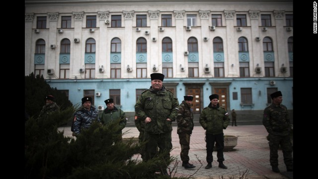 Cossacks and other pro-Russian forces stand guard outside a government building in Simferopol on Saturday, March 8.