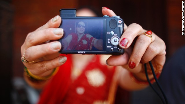 MARCH 10 - KATHMANDU, NEPAL: A Nepalese woman takes a selfie outside a temple. People around the world marked International Women's Day on Saturday, celebrating women's achievements and campaigning for gender equality. Joining them was <a href='http://edition.cnn.com/2014/03/08/living/cnnwomen-tweetchat-as-it-happened/index.html'>CNN's Leading Women team which hosted a global discussion on equality</a>.