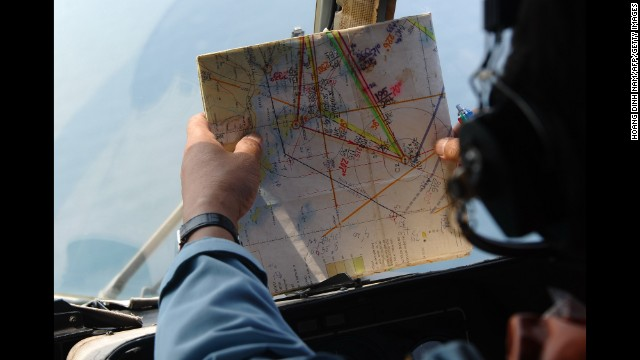 A member of the Vietnamese air force checks a map while searching for the missing plane on Tuesday, March 11.