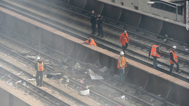 Workers inspect debris on the Metro North railroad tracks near the scene of the explosion.