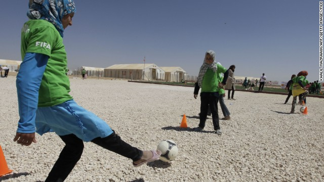 A group of young girls wearing one of the FIFA shirts enjoy kicking a ball.