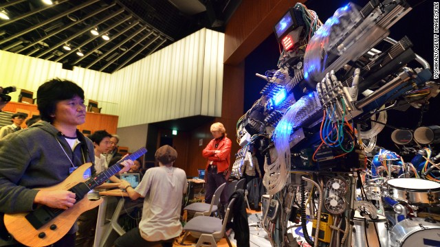 A man plays an electric guitar to control robot guitarist 'March' during a technology fair in Tokyo. What will the future hold for electronic music?