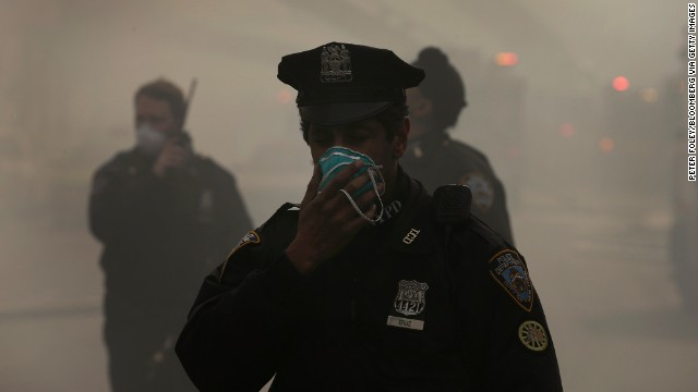 A police officer covers his face with a mask to protect himself from the smoke.