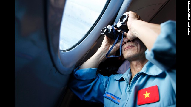 A Vietnamese military official looks out a plane above Vietnam's sea Thursday in the search for the missing Malaysia Airlines jet.