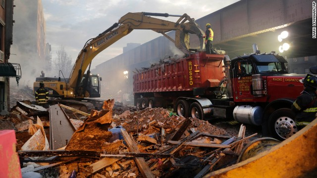An excavator removes debris on Thursday, March 13, from the site of a massive explosion.