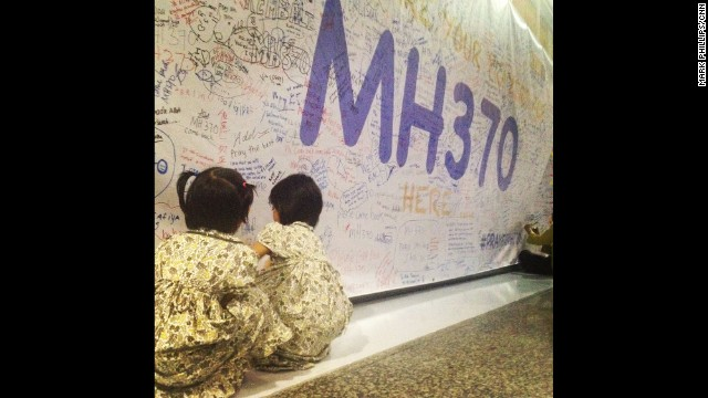 Two young girls leave messages and well-wishes for those on board the missing Malaysia Airlines plane on the walls of Kuala Lumpur International Airport. By CNN's Mark Phillips, March 13. Follow Mark on Instagram at instagram.com/markpcnn.