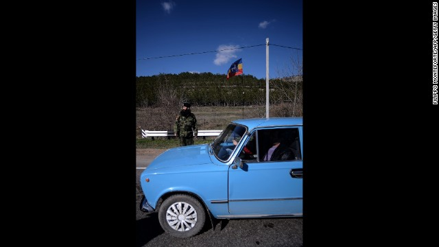 An armed Cossack stands guard at a checkpoint on the road from Simferopol to Sevastopol on March 13. Security measures are tightening around Simferopol, Crimea's capital, as the pro-Russian regional government prepares to hold a referendum to break away from Ukraine. The standoff has revived concerns of a return to Cold War relations.