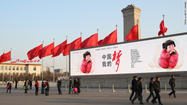 In Beijing, citizens walk by a large banner reading