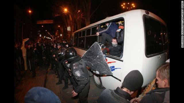 A line of policemen stand in front of a bus of pro-Ukrainian activists as pro-Russian supporters confront them during a rally in Donetsk on Thursday, March 13.