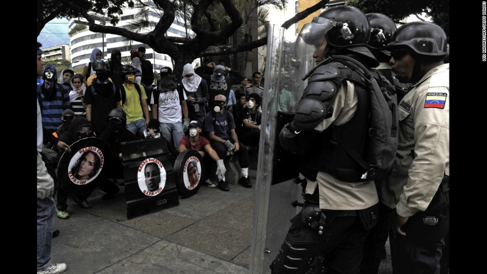 Anti-government activists, left, face riot police in Caracas, Venezuela, on Thursday, March 13. For weeks, anti-government protesters, unhappy with the economy and rising crime, have been clashing with security forces.