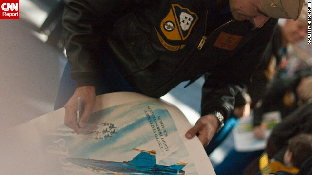 A pilot signs a poster for a fan.
