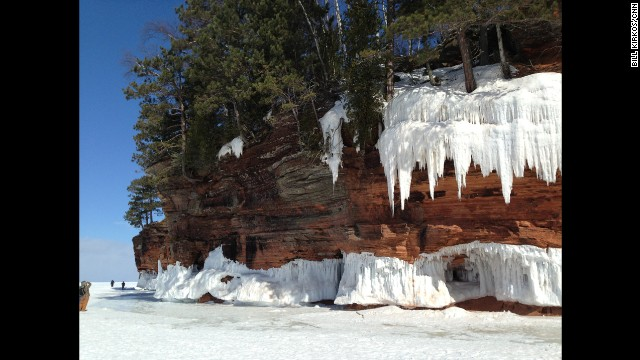 Snow and ice dangle over Lake Superior, covering the edge of a cliff.