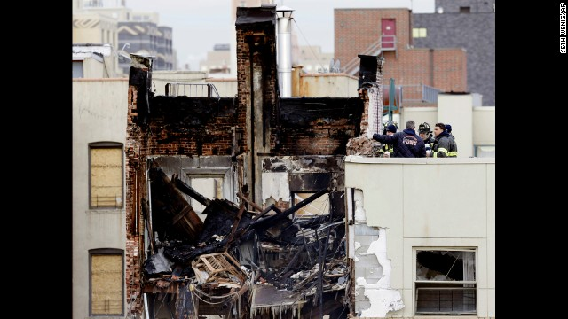 Firefighters look over what remains of a building affected by the explosion on March 14.