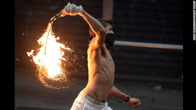 A demonstrator throws a Molotov cocktail during clashes with members of the National Guard during a protest against Venezuelan President Nicolas Maduro in Caracas, Venezuela, on Saturday, March 15. For weeks, anti-government protesters, unhappy with the economy and rising crime, have been clashing with security forces.
