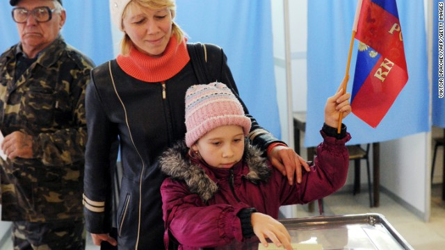 A child casts her mother's ballot while holding a Russian flag at a polling station on Sunday, March 16, in Simferopol. Polls opened Sunday morning in a referendum in Ukraine's Crimea region, in which voters are to voice their wish to either join Russia or become an effectively independent state connected to Ukraine.