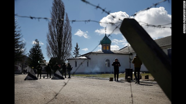 Armed soldiers stand guard outside a Ukrainian military base in Perevalne on March 17.