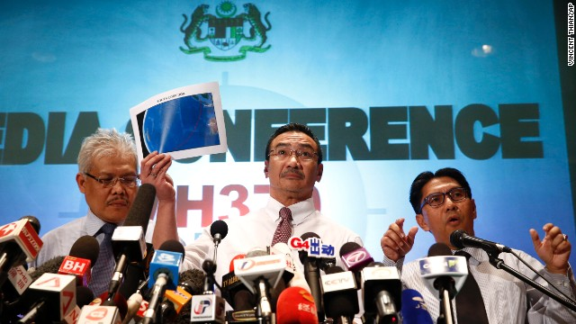 Malaysian Transportation Minister Hishamuddin Hussein, center, shows maps of the search area at a hotel next to the Kuala Lumpur International Airport on March 17.