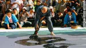 A calligraphy master uses a giant brush to put on a show at the annual Kumano Brush Festival.