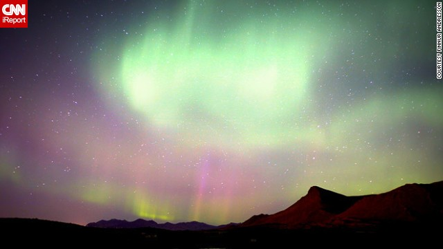 The Northern Lights dance through the nighttime sky over Akranes, Iceland.