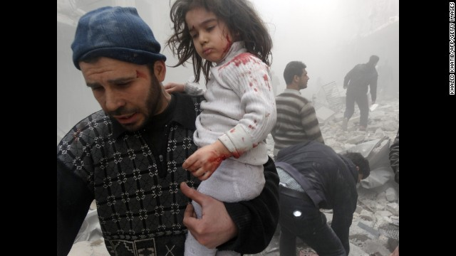 A man carries a child who was found in the rubble of an Aleppo, Syria, building after it was reportedly bombed by government forces on Monday, March 18.
