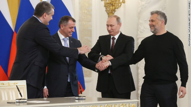 From left, Crimean Prime Minister Sergey Aksyonov; Vladimir Konstantinov, speaker of the Crimean parliament; Russian President Vladimir Putin; and Alexei Chaly, the new de facto mayor of Sevastopol, join hands in Moscow on March 18 after signing a treaty to make the Black Sea peninsula part of Russia.