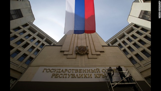 A Russian flag waves as workers install a new sign on a parliament building in Simferopol, Crimea's capital, on March 19.
