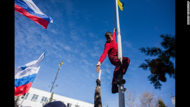 A member of pro-Russian forces takes down a Ukrainian flag at the Ukrainian navy headquarters in Sevastopol on March 19.