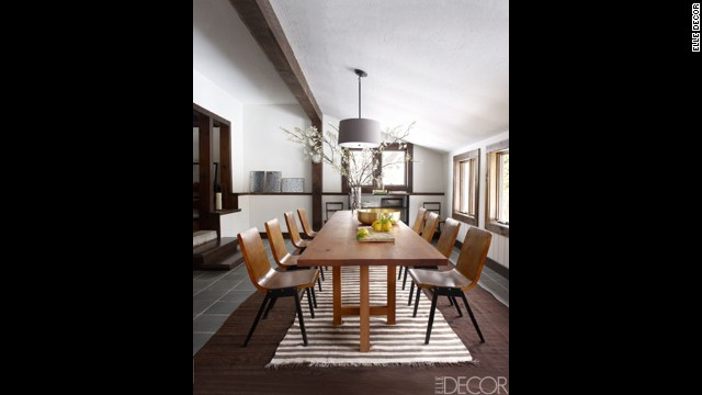 In the dining room: Vintage chairs from R. T. Facts surround the dining table, which was made from a cherry tree on the property; the light fixture is by Restoration Hardware, the rugs are Moroccan, and the flooring is slate.