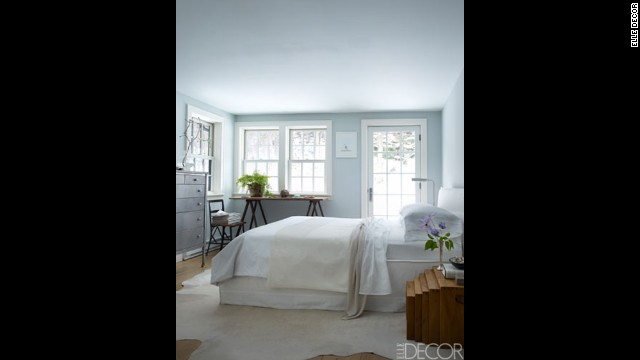 In the master bedroom: The bed and linens in the master bedroom are by Calvin Klein Home, the nesting tables are from Margaret Howell, the desktop was made from wood found in the shed, and the chair is a flea-market find; the rug is by Moore & Giles, and the walls are painted in Benjamin Moore Aura in Sterling.