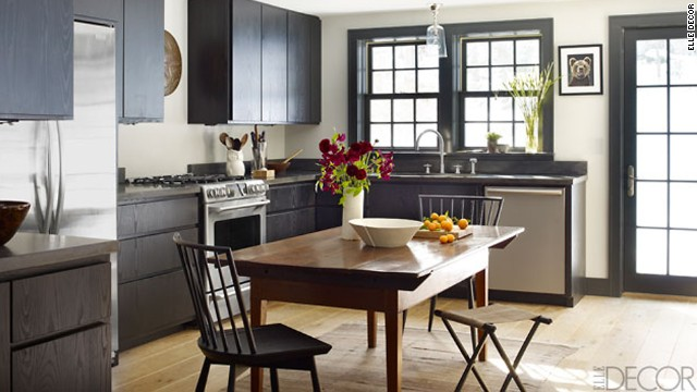 In the kitchen, the antique walnut table is American, and the chairs and stool are by Calvin Klein Home; the cabinets are custom made, the refrigerator is by KitchenAid, the oven is by GE, and the dishwasher is by Bosch.