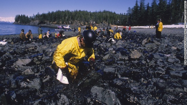 A Valdez worker wipes oil off the rocks on the shoreline.