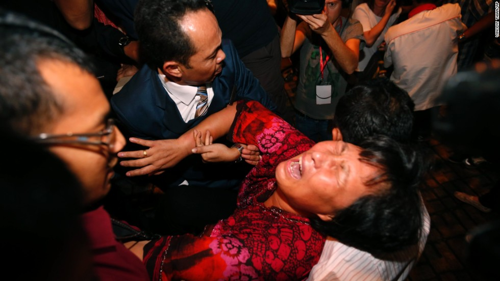 A distraught relative of a passenger on the missing <a href='http://www.cnn.com/2014/03/07/asia/gallery/malaysia-airliner/index.html'>Malaysia Airlines Flight 370</a> is carried out by security officials before a press conference in Sepang, Malaysia, on Wednesday, March 19. The plane disappeared during a March 8 flight from Kuala Lumpur to Beijing.