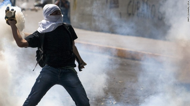 A person holds a smoking canister as demonstrators clash with members of the National Police on March 20 in Caracas.