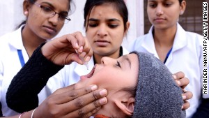 An child receives polio vaccination drops from a medical volunteer in Amritsar, India, on January 19.