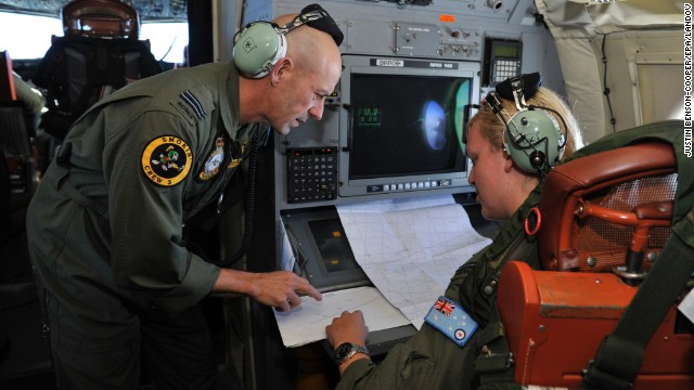 The Royal Australian Air Force's Neville Dawson, left, goes over the search area with Brittany Sharpe aboard an AP-3C Orion some 2,500 kilometers (about 1,500 miles) southwest of Perth, Australia, over the Indian Ocean on March 21.