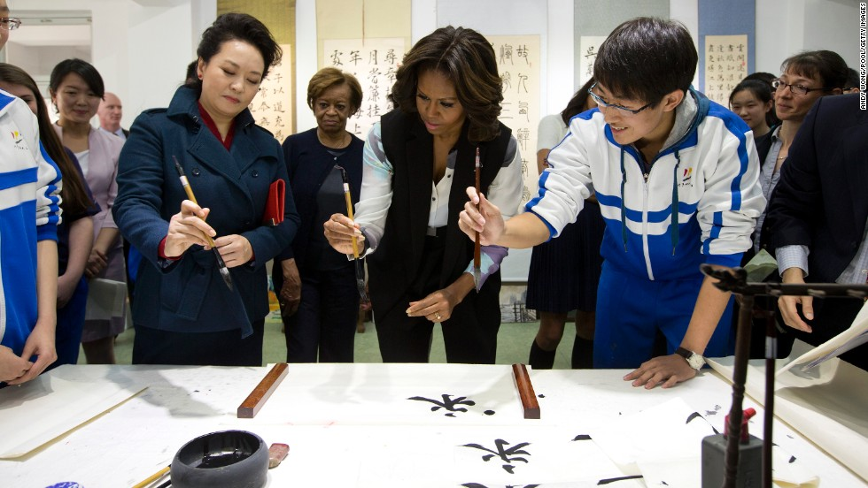 Peng Liyuan, wife of Chinese President Xi Jinping, left, shows first lady Michelle Obama how to hold a writing brush as they visit a Chinese traditional calligraphy class in Beijing on Friday, March 21. The first lady is on <a href='http://www.cnn.com/2014/03/21/politics/gallery/michelle-obama-china/index.html'>an official visit</a> to expand relations between the United States and China. Click through the gallery to see her other international travels through the years.