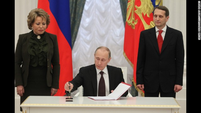 Russian President Vladimir Putin signs the final decree completing the annexation of Crimea on Friday, March 21, as Upper House Speaker Valentina Matviyenko, left, and State Duma Speaker Sergei Naryshkin watch.