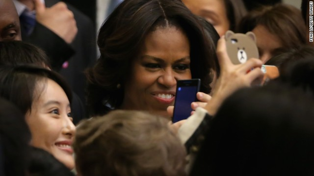 A Chinese student takes pictures with her phone besides first lady Michelle Obama, center, after Mrs. Obama spoke at the Stanford Center at Peking University on March 22 in Beijing, China.