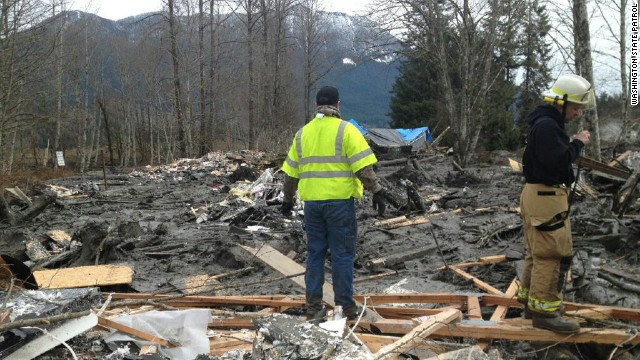 Emergency workers arrive at the scene of the landslide.