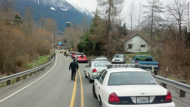 Police cars and other vehicles line the highway near the scene of the landslide.