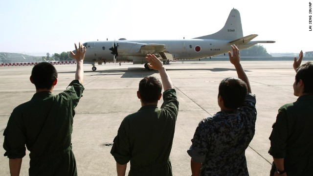 Ground crew members wave to a Japanese Maritime Defense Force patrol plane as it leaves the Royal Malaysian Air Force base in Subang, Malaysia, on Sunday, March 23. The plane was heading to Australia to join a search-and-rescue operation.
