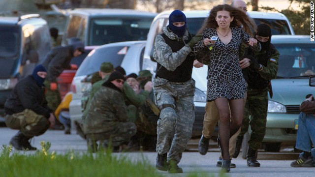 Pro-Russian militia members remove a local resident as Russian troops assault the Belbek air base, outside Sevastopol, on Saturday, March 22. Following its annexation of Crimea, Russian forces have consolidated their control of the region.